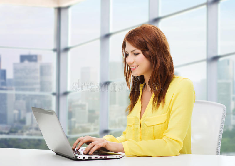 Mulher nova de sorriso com computador portátil fotos de stock