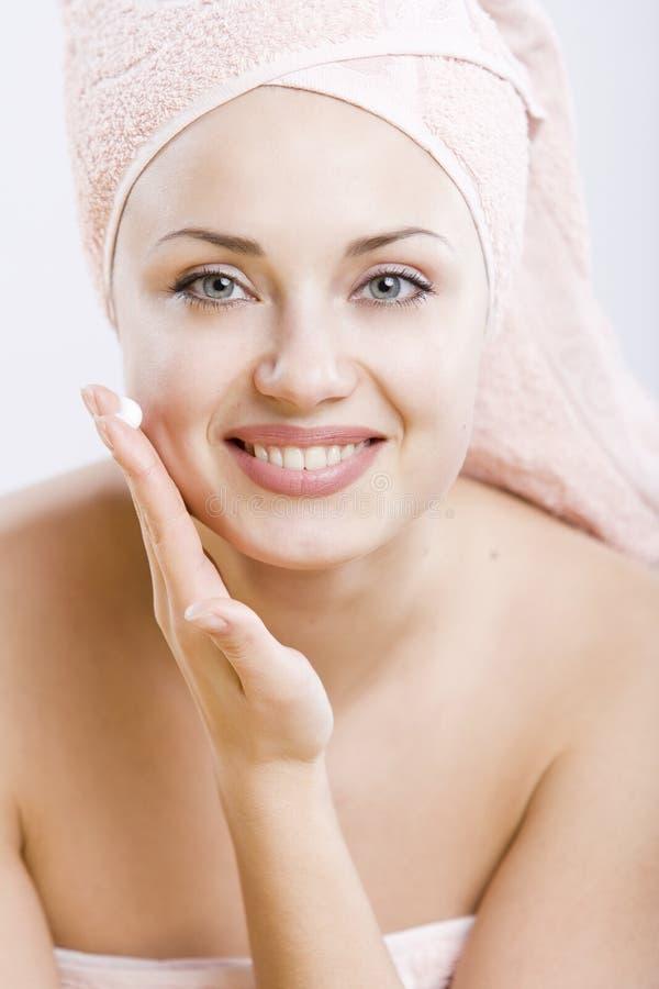 Mulher nova de sorriso com creme facial em sua mão imagem de stock