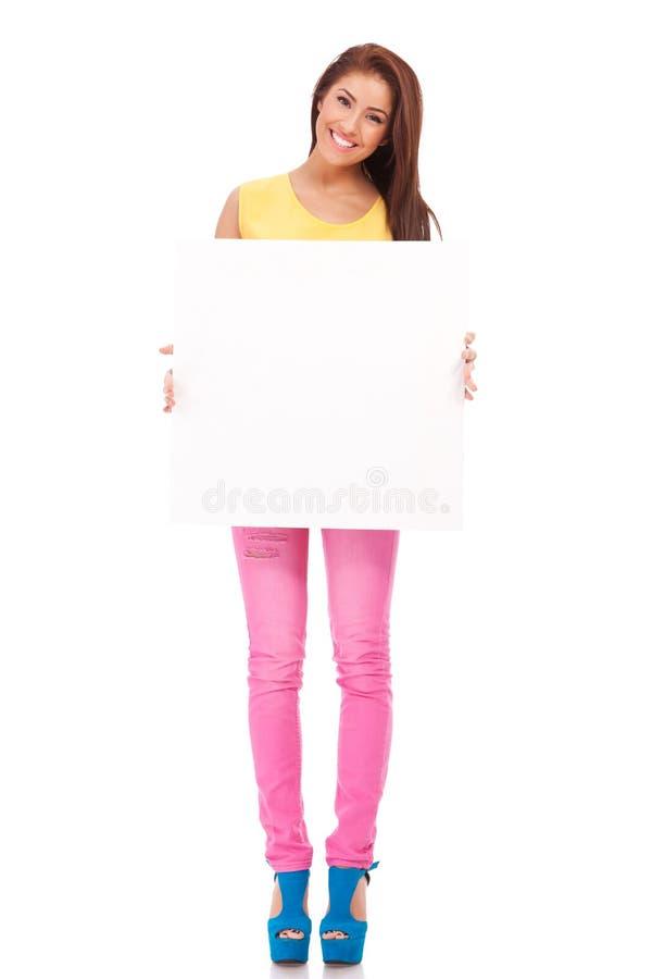 Mulher nova de sorriso com placa de conta em branco foto de stock royalty free