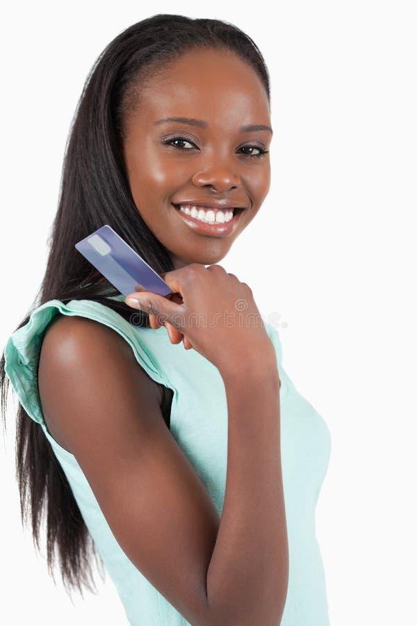 Mulher nova de sorriso com seu cartão de crédito imagem de stock