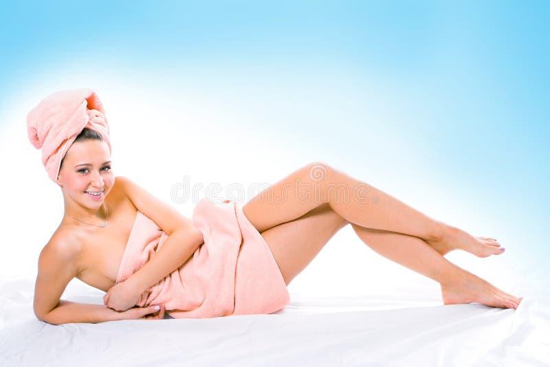 Mulher nova de sorriso da beleza na toalha imagem de stock