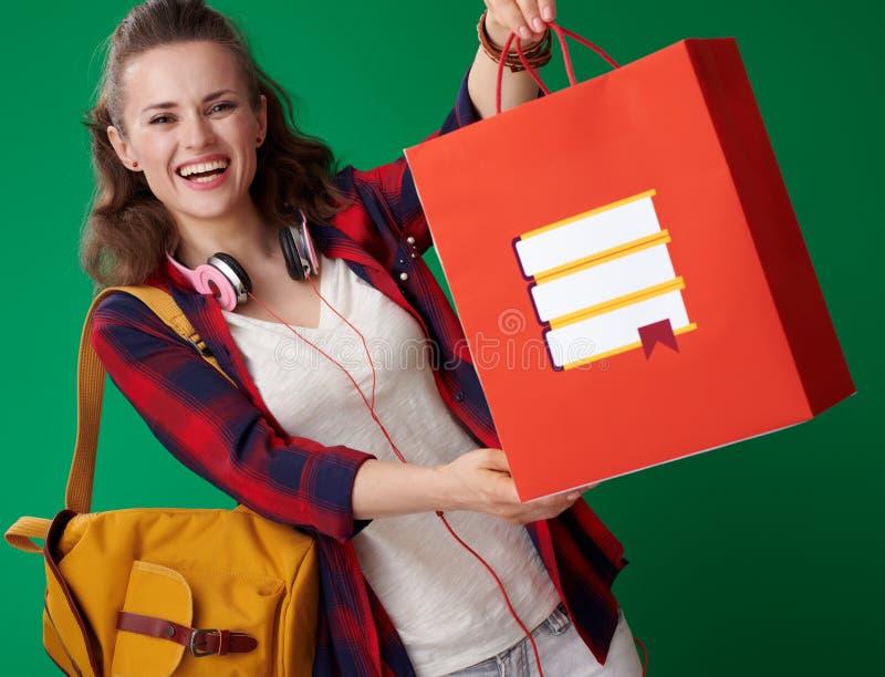 Mulher nova de sorriso do estudante que dá o saco de compras com livros fotos de stock