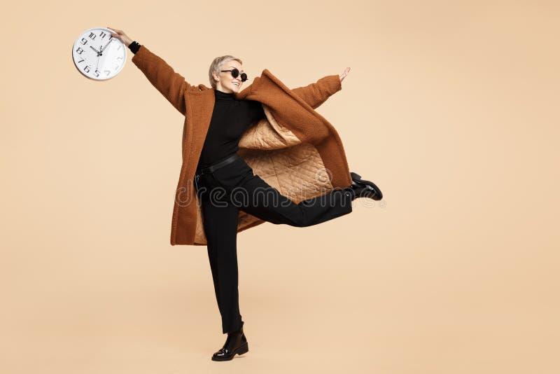 A mulher nova de sorriso do moderno com o cabelo curto louro que veste um revestimento e os óculos de sol dançam com o pulso de d fotos de stock