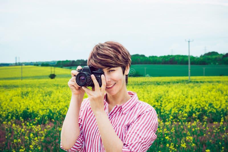 Mulher nova de sorriso do moderno que toma fotos com a câmera retro do filme no campo amarelo de florescência Capture o momento C fotografia de stock royalty free