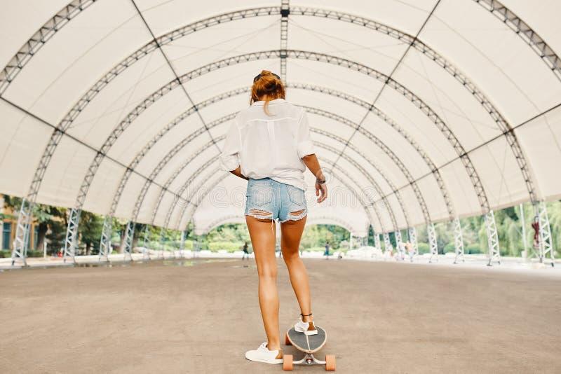 Mulher nova de sorriso do skater que monta seu longboard na cidade imagem de stock royalty free