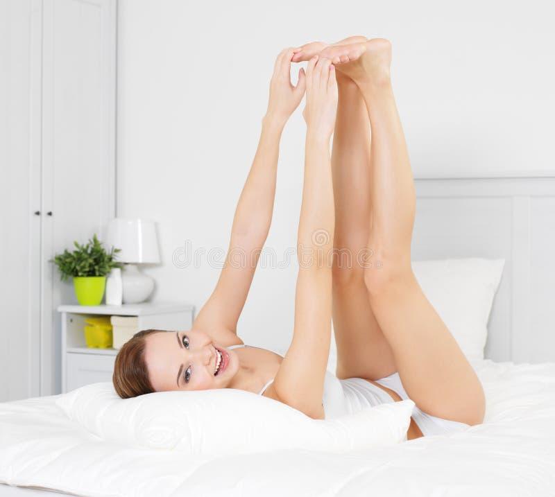 Mulher nova de sorriso feliz com pés bonitos fotografia de stock royalty free