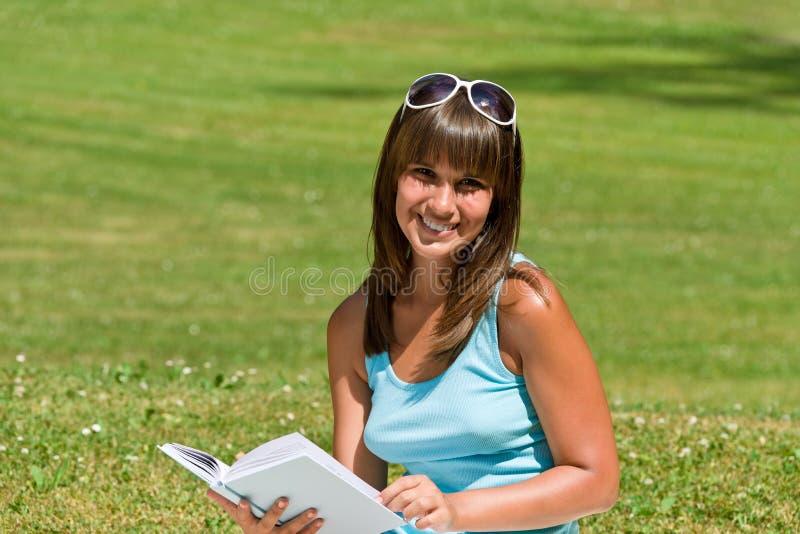 A mulher nova de sorriso leu o livro no parque imagens de stock royalty free