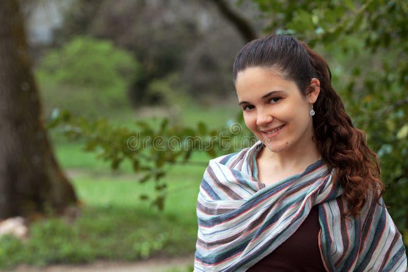 Mulher nova de sorriso no parque fotografia de stock