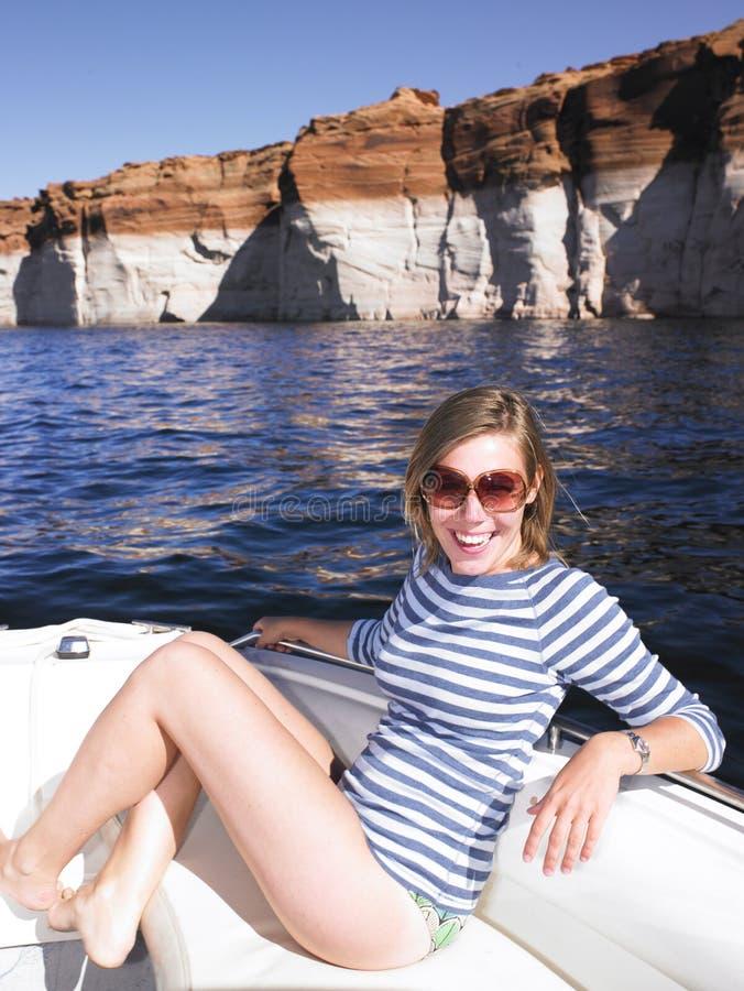 Mulher nova de sorriso que senta-se no barco fotos de stock royalty free