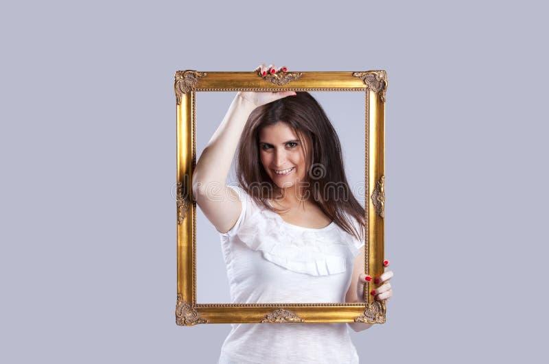 Mulher nova dentro de um frame de retrato imagens de stock royalty free