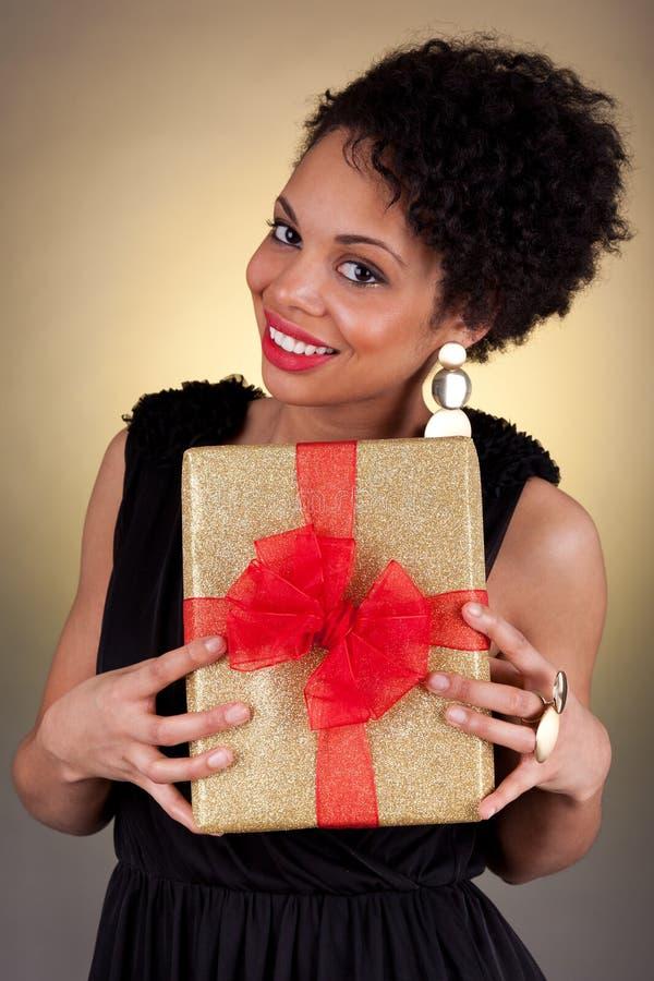 Mulher nova do americano africano que prende um presente imagens de stock royalty free