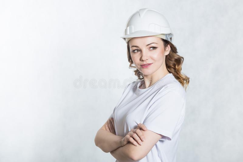 Mulher nova do arquiteto no capacete de segurança branco do capacete de segurança no fundo branco fotos de stock royalty free