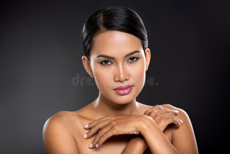 Mulher nova do Balinese que toca em sua pele imagens de stock