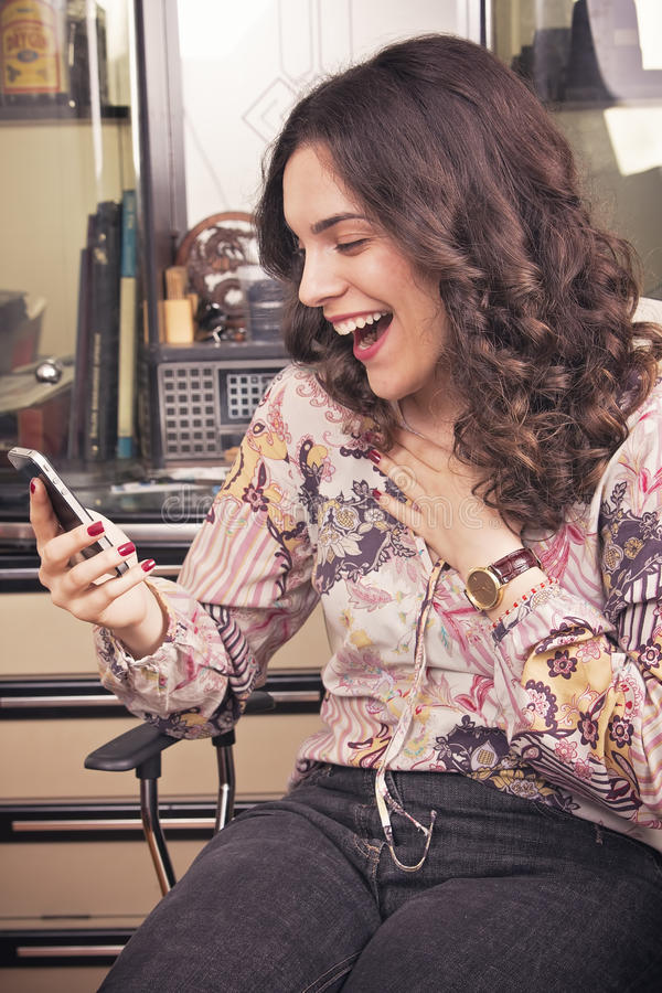 Mulher nova do beautfiul que ri a uma mensagem de telefone foto de stock
