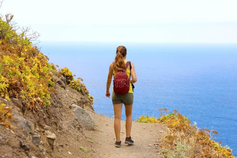 Mulher nova do caminhante que anda em uma fuga que negligencia o mar em Tenerife foto de stock
