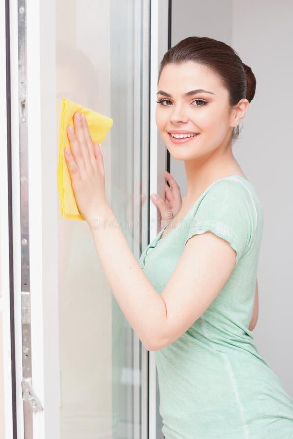 Mulher nova do camponês que limpa a janela imagens de stock