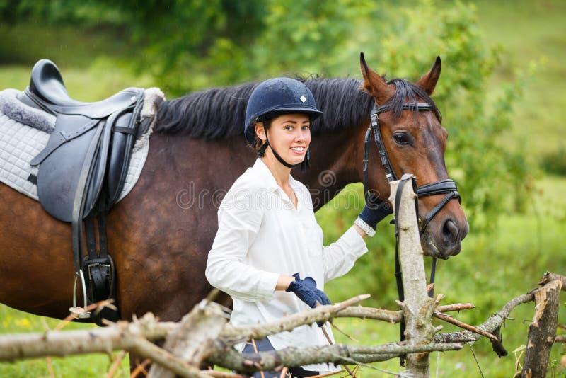Mulher nova do cavaleiro no capacete que guarda o cavalo de baía imagens de stock royalty free