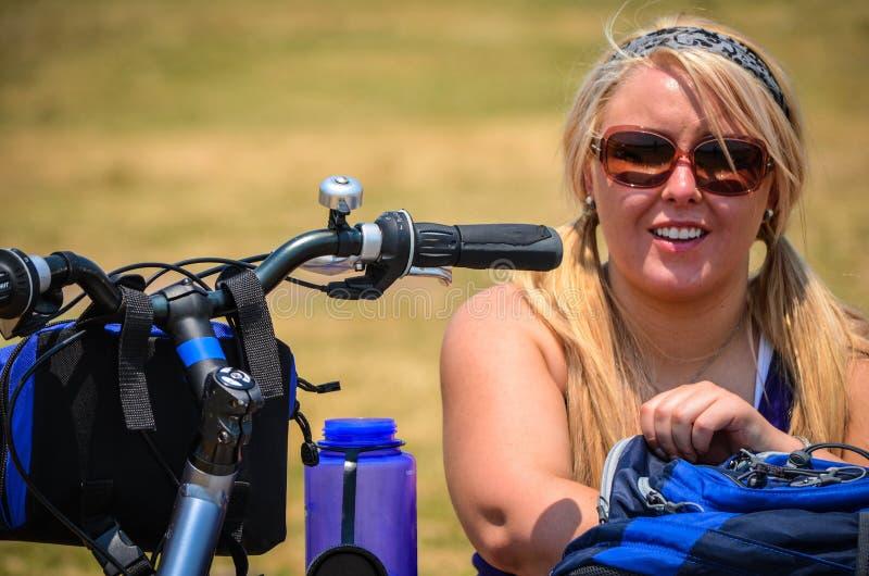 A mulher nova do ciclista toma uma ruptura de montar uma bicicleta para alcançar em sua trouxa A menina está sorrindo e feliz fotografia de stock royalty free