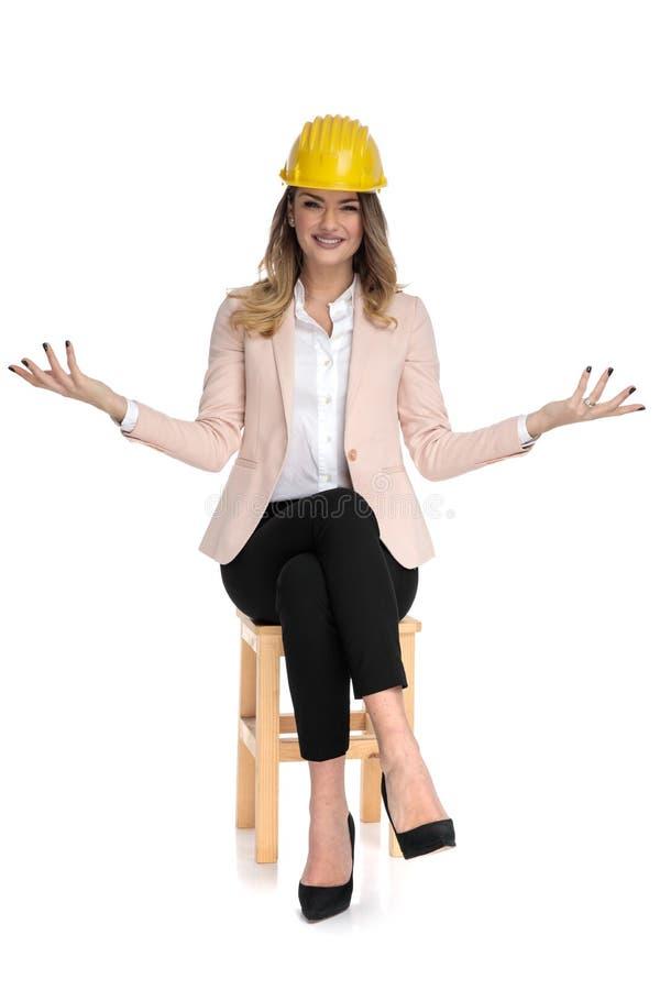 A mulher nova do coordenador senta e faz o gesto de convite fotos de stock