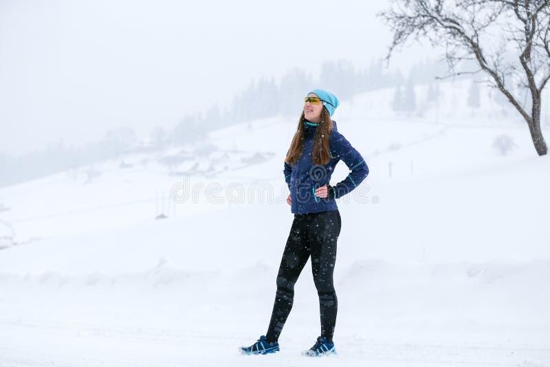 Mulher nova do corredor que está na estrada no inverno foto de stock royalty free