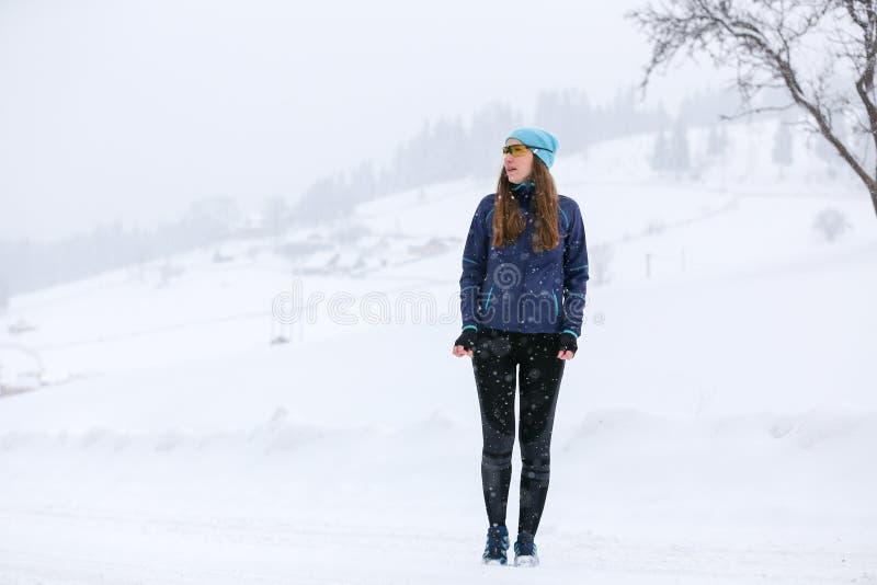 Mulher nova do corredor que está no parque no inverno imagens de stock royalty free