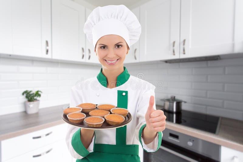 Mulher nova do cozinheiro chefe na bandeja guardando uniforme com queques e polegares imagens de stock royalty free