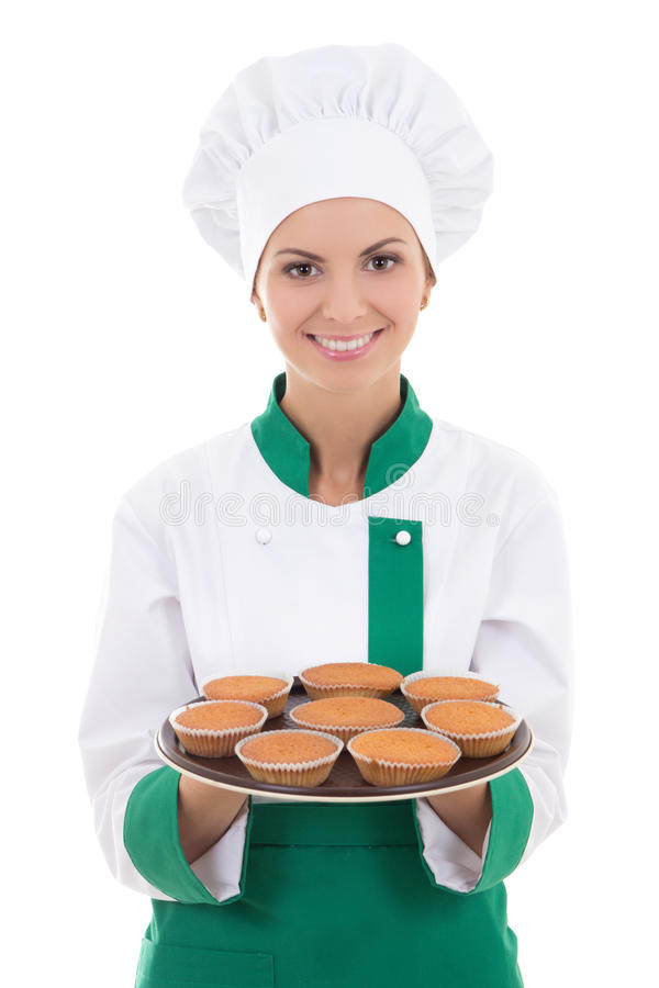 A mulher nova do cozinheiro chefe na bandeja mostrando uniforme com queques isolou o foto de stock royalty free