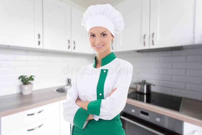 Mulher nova do cozinheiro chefe no uniforme que está na cozinha moderna imagem de stock royalty free