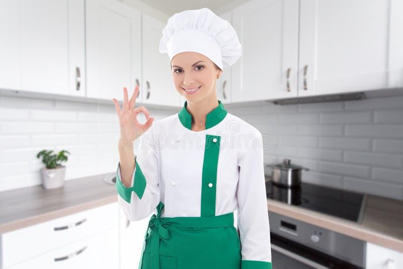 A mulher nova do cozinheiro chefe no uniforme que mostra está bem assina dentro a cozinha moderna imagem de stock royalty free
