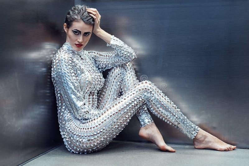 Mulher nova do cyber no traje futurista de prata que senta-se no elevador foto de stock royalty free