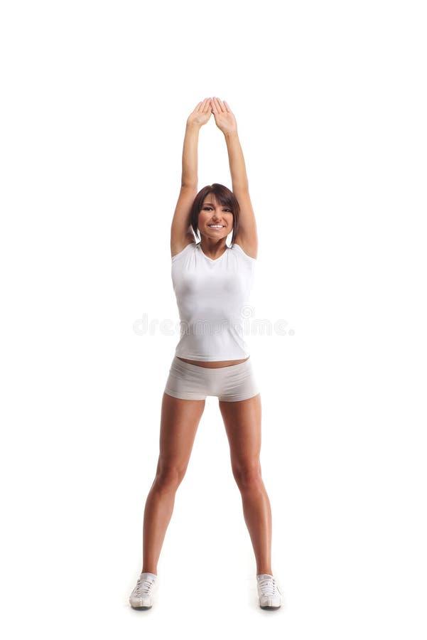 Mulher nova do esporte que faz os exercícios isolados no branco foto de stock royalty free