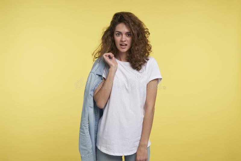A mulher nova do estudante está com a camisa de calças de ganga sobre ela para trás com olhar bonito ao sentido oposto imagem de stock royalty free