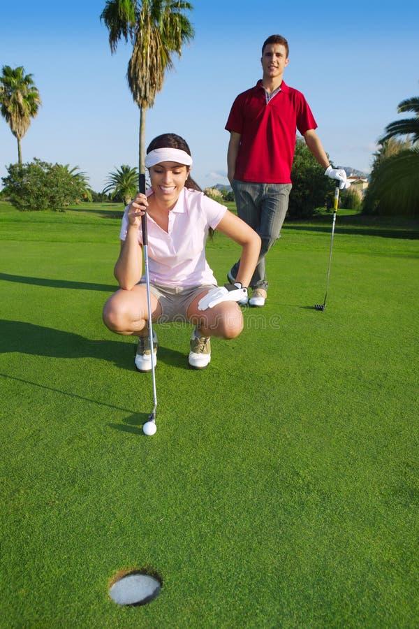Mulher nova do golfe que olha e que aponta o furo imagens de stock
