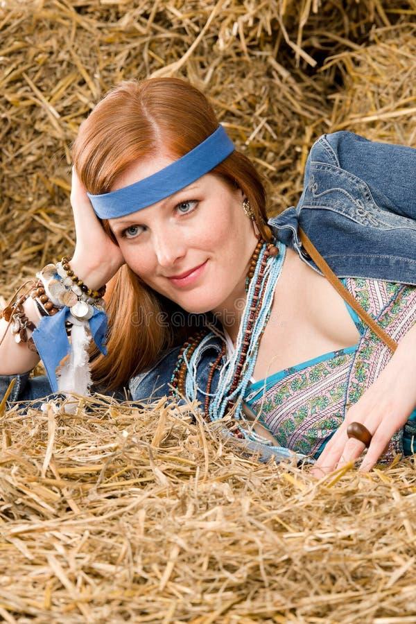 A mulher nova do hippie que encontra-se no feno relaxa fotografia de stock