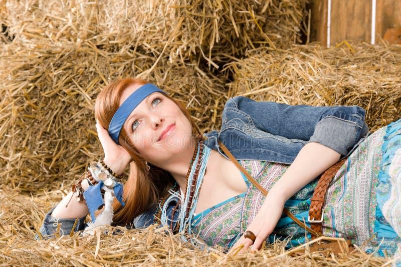 A mulher nova do hippie que encontra-se no feno relaxa imagem de stock royalty free