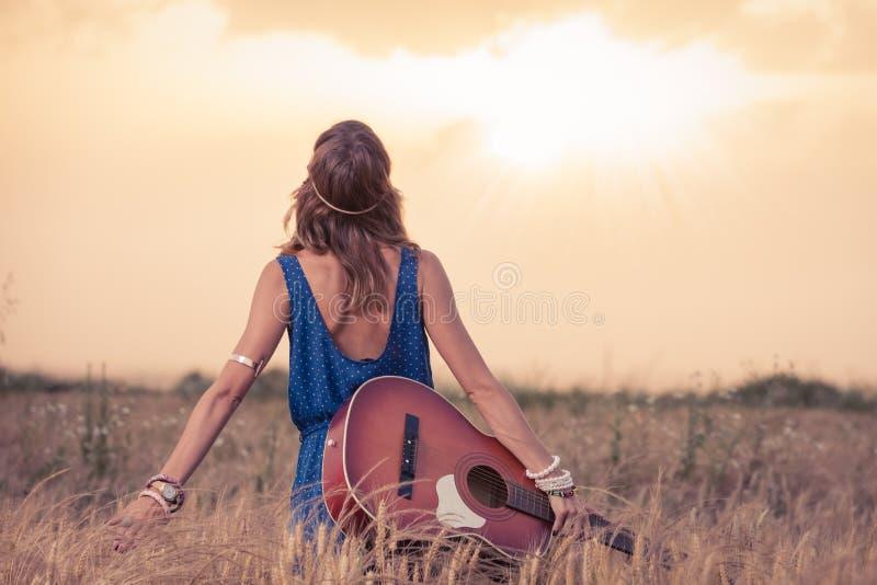 Mulher nova do hippy com guitarra acústica que aprecia o por do sol fotos de stock