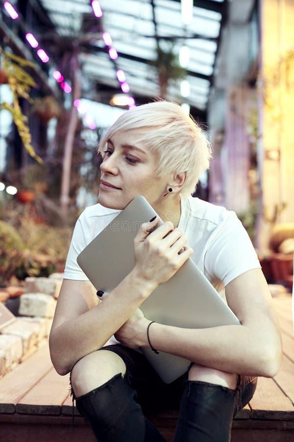 Mulher nova do moderno com o cabelo curto louro que senta-se nas escadas, guardando o laptop moderno imagem de stock