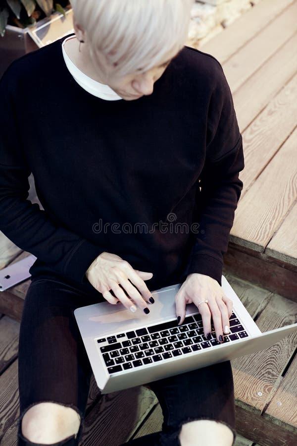 A mulher nova do moderno com o cabelo curto louro que senta-se nas escadas, trabalhando no laptop moderno, olha para baixo, tecla fotos de stock royalty free