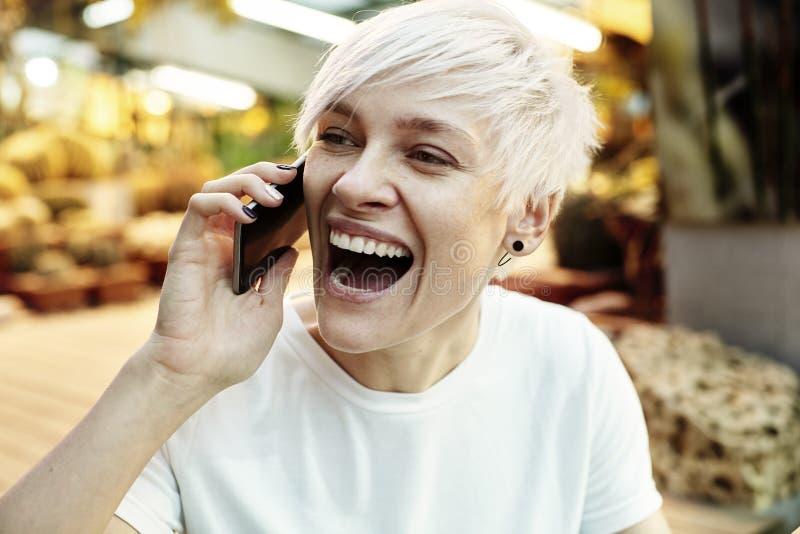 Mulher nova do moderno com o cabelo curto que coloca em alguém que usa o telefone celular imagens de stock royalty free