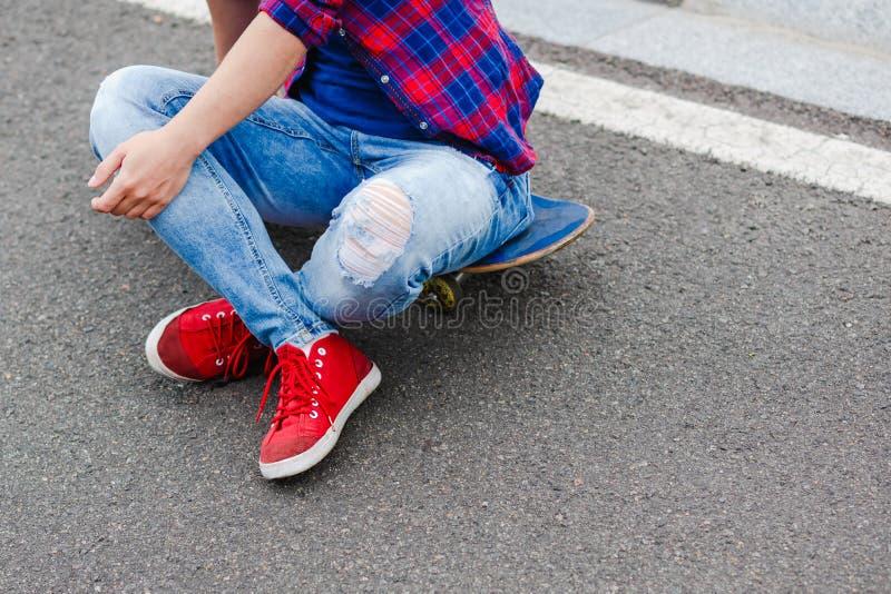 Mulher nova do moderno com placa de patinagem na estrada imagem de stock