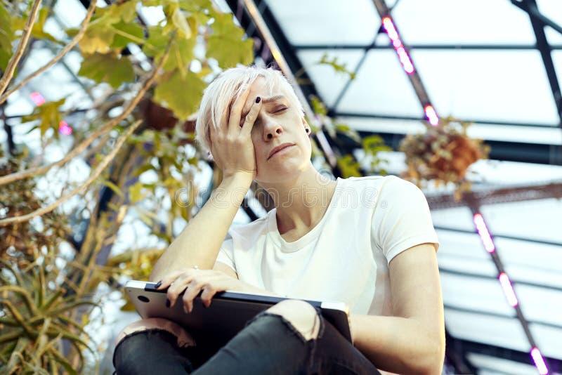 Mulher nova do moderno com a sensação loura do cabelo curto cansado e virada com o portátil, sentando-se em escadas Interior inte foto de stock royalty free