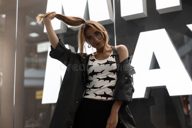 A mulher nova do moderno na roupa na moda em vidros à moda com penteado na moda está e mantém o cabelo perto da parede de vidro b foto de stock