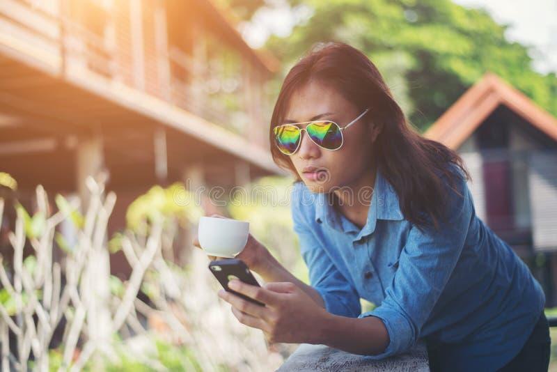 Mulher nova do moderno que olha seu telefone ao guardar um copo de fotos de stock royalty free