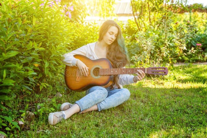 Mulher nova do moderno que senta-se na grama e que joga a guitarra no fundo do parque ou do jardim Menina adolescente que aprende imagens de stock royalty free