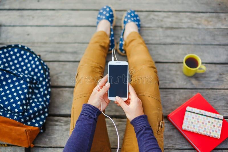 Mulher nova do moderno que usa o telefone esperto exterior imagem de stock royalty free