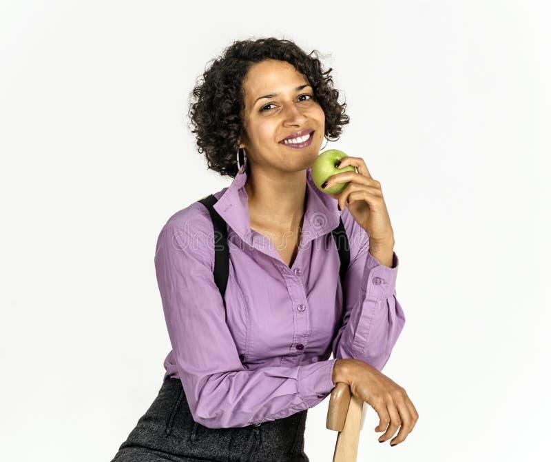 A mulher nova do mulato em um terno de negócio come a maçã imagem de stock royalty free