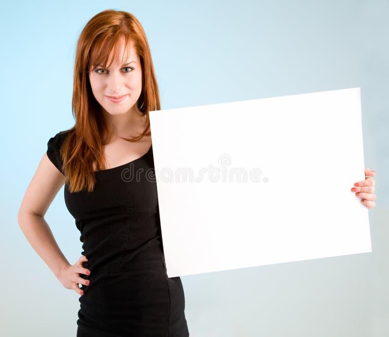 Mulher nova do Redhead que prende um sinal branco em branco imagem de stock