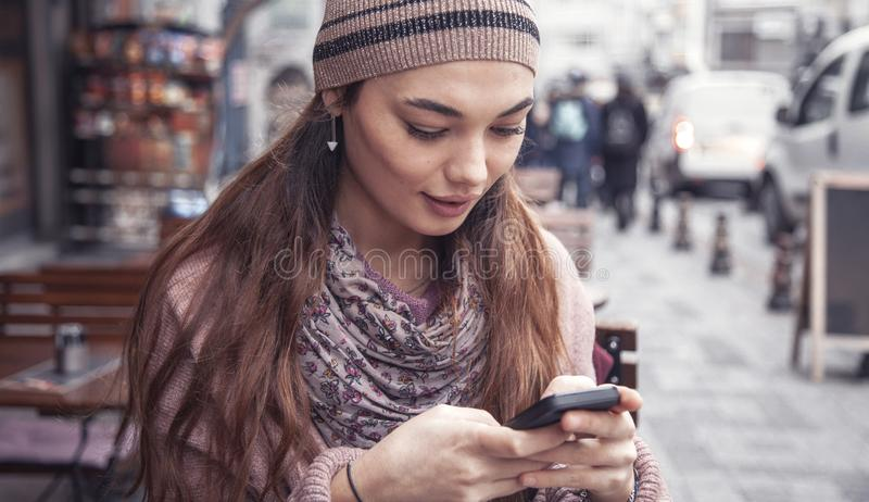 Mulher nova do retrato que usa o telefone celular no ar livre fotografia de stock
