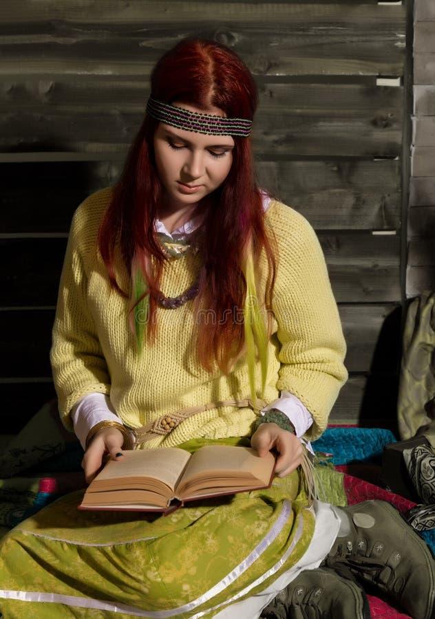 A mulher nova do ruivo do boho da hippie leu o livro em um fundo de madeira da parede foto de stock royalty free