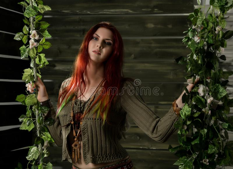 Mulher nova do ruivo do boho da hippie que tem o divertimento em um balanço Estilo da hippie em um fundo de madeira fotografia de stock royalty free